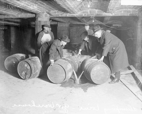 Agentes do governo no ato de confiscar e descartar bebidas clandestinas (Chicago, 1921).