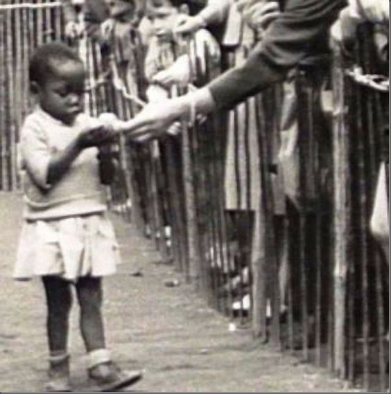 """Menininha africana sendo alimentada na """"Vila Africana"""" em Bruxelas, Bélgica , em 1958"""